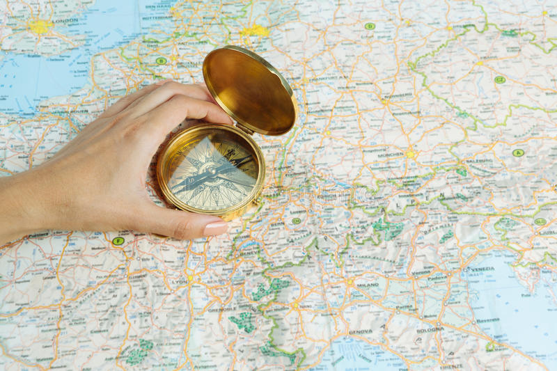 Importance to know the right direction. Hand with a compass on a table with map. metaphor of the crossroads in life stock images