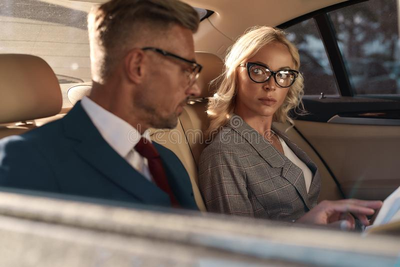 Important business meeting. Young and beautiful woman in eyeglasses looking at her business partner and dicussing royalty free stock images