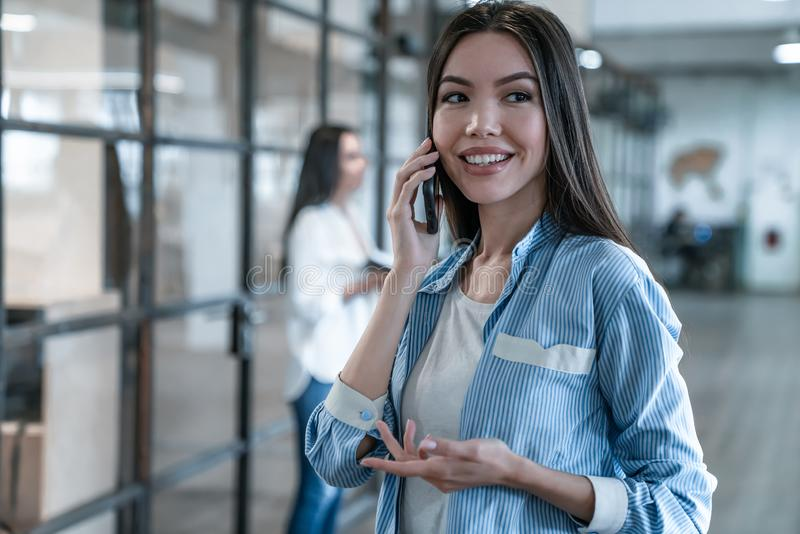 Important business talk. Beautiful young asian woman talking on the mobile phone and smiling while standing in modern office royalty free stock photos