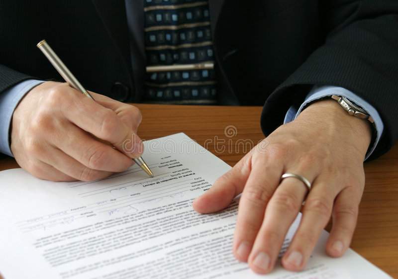 Important man-important paper. Well dressed man signing a doc.or filling out form royalty free stock image