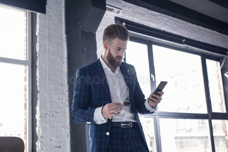 Horizontal shot. Important message. Handsome young man in full suit holding a smart phone by standing at home royalty free stock image