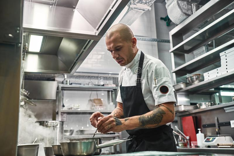 Important moment. Serious professional chef in apron, with several tattoos on his hands cooking in a restaurant kitchen royalty free stock photos