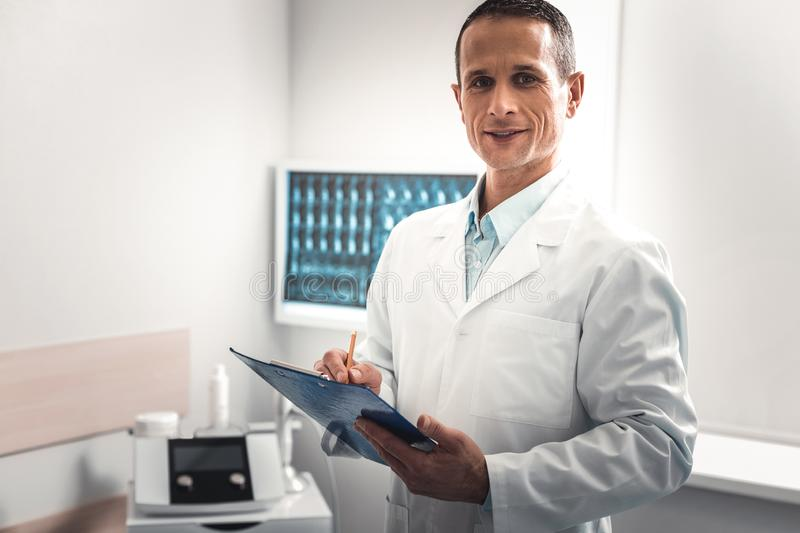 Dark-haired doctor making some important notes royalty free stock photos