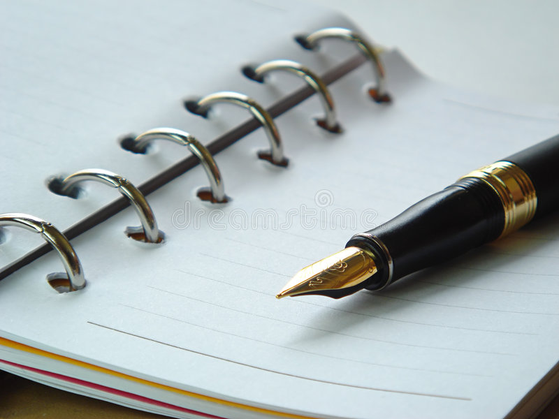 Important writings. Blank spiraled notebook with fountain pen on top of it stock photo