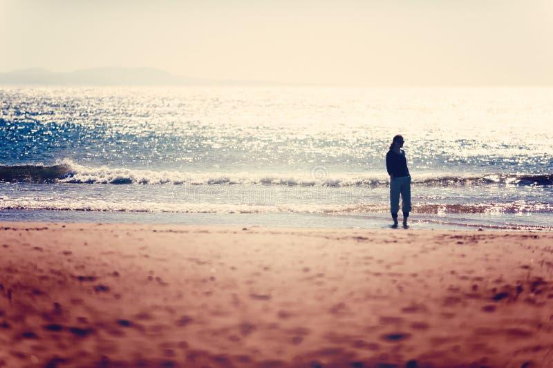 Importe-se a mulher livre que toma uma caminhada antes do por do sol na praia de Essaouira imagem de stock