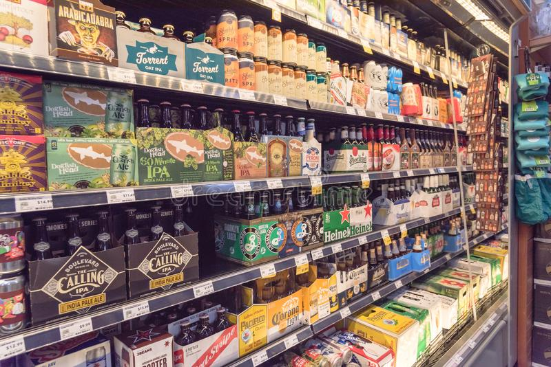 Imported beers at Whole Foods store. HOUSTON, TEXAS, US - DEC 9, 2017: Various bottles of craft, microbrews, IPAs imported beers from around the world on shelf stock photography