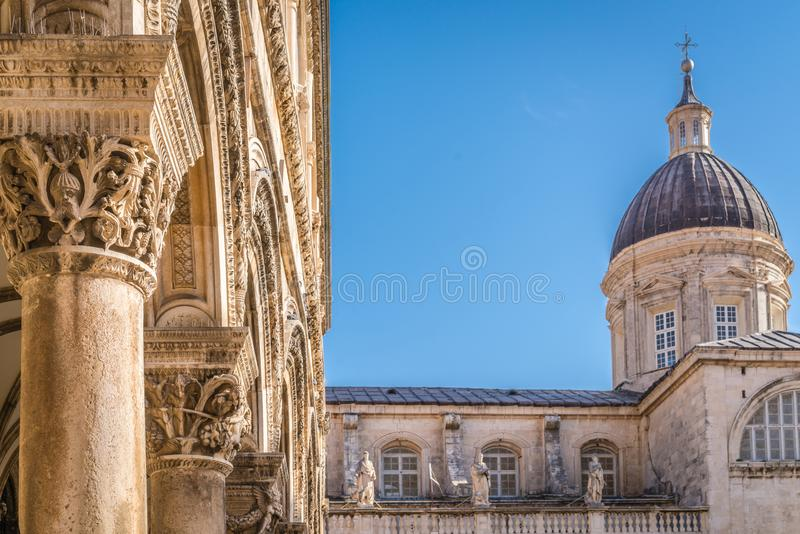 Imposing Church tower dome in Dubrovnik. Imposing Church tower dome and close up of the arched roof supporting columns with carved figures, Dubrovnik Old Town stock photography