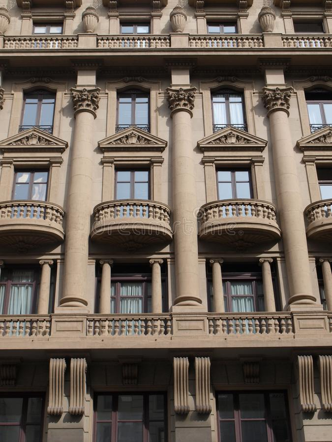 Imposing façade of a stone building. In Barcelone center,  monumental façade of a building. Three rows of high windows with stone balconies and triangular stock image