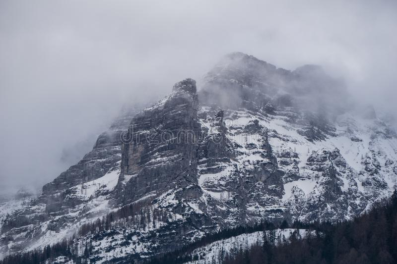 Imposing landscape in the Austrian Alps with towering cliffs engulfed in clouds and fog stock photo