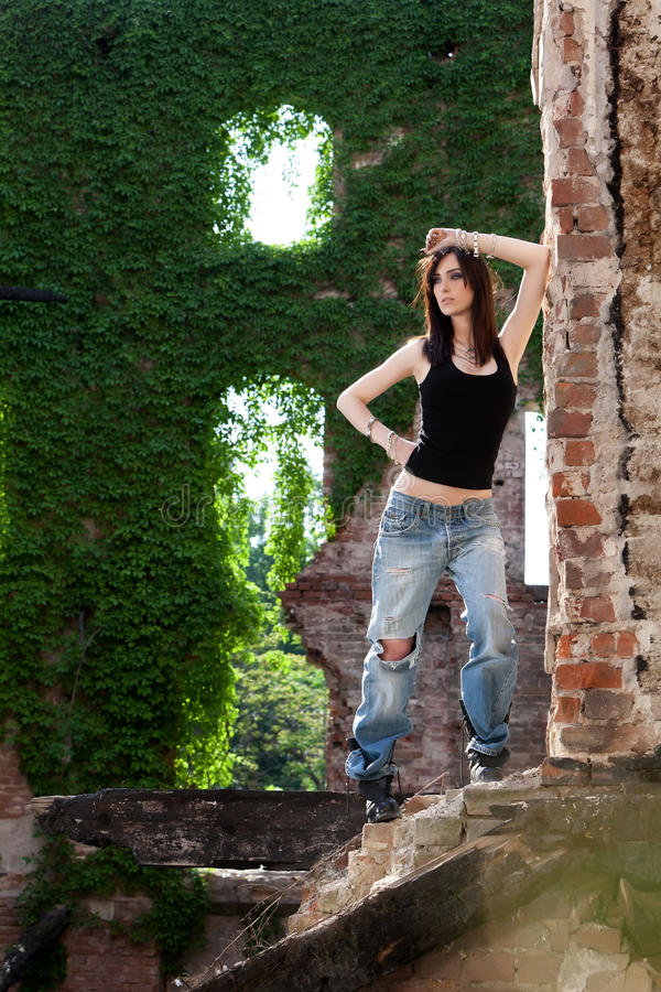 Impossible is not in my dictionary. Beautiful and mysterious brunette with a strong active attitude with green ivy in the backround royalty free stock photography