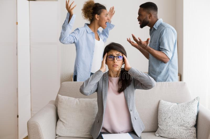 Puzzled Relationship Coach Witnessing Her Patients Arguing In Her Office. Impossible Reconciliation. Shocked Counselor Witnessing Angry Afro Couple Shouting At royalty free stock photography