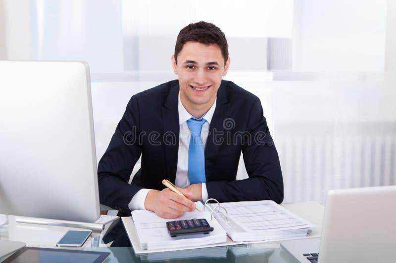 Imposto calculador de sorriso do homem de negócios fotos de stock royalty free
