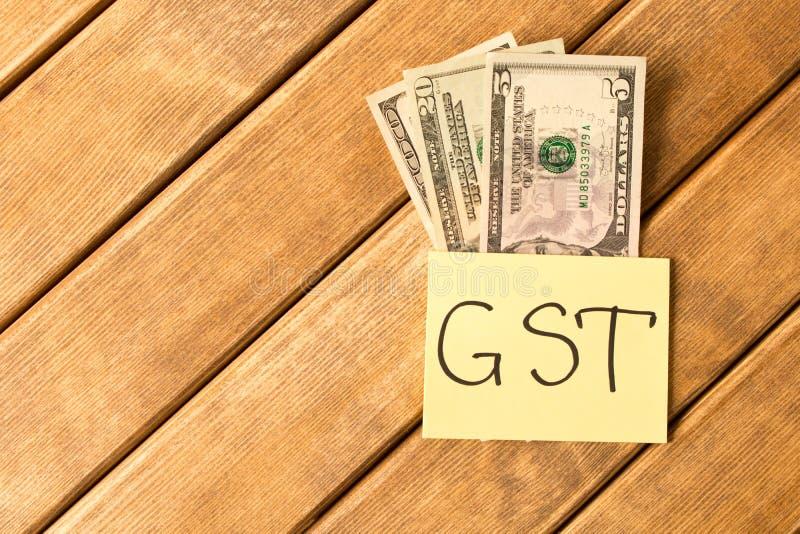 Imposto do produtos e serviços Inscrição de GST com as cédulas no woode imagem de stock royalty free