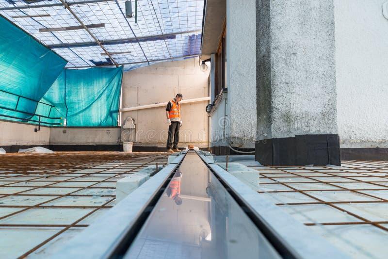 Imprägnierung und Wärmedämmung einer Terrasse - Dach Eine Berufsarbeitskraft installiert einen Abflusssinkkasten für Entwässerung stockfotografie