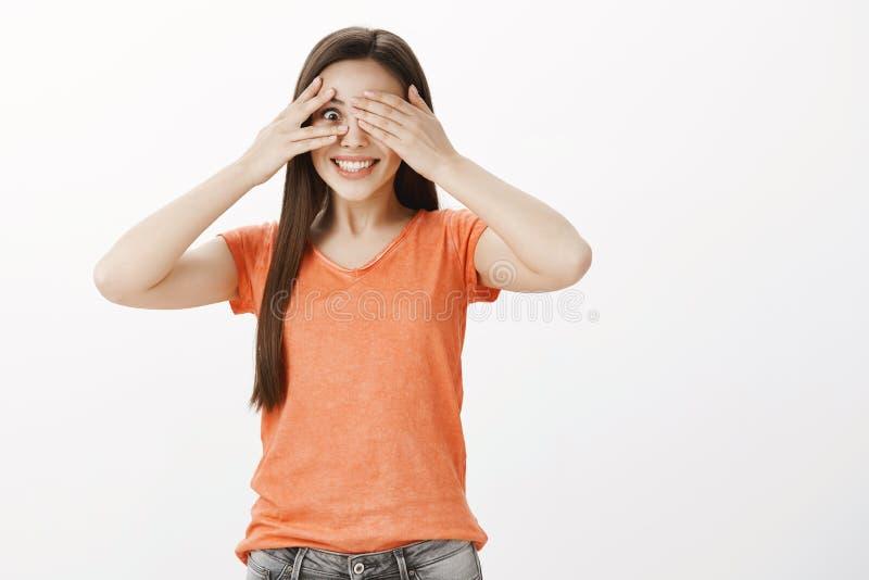 Impratient咧嘴笑的女孩不可能等待看惊奇的礼物 橙色T恤杉的惊奇悦目欧洲妇女 库存图片
