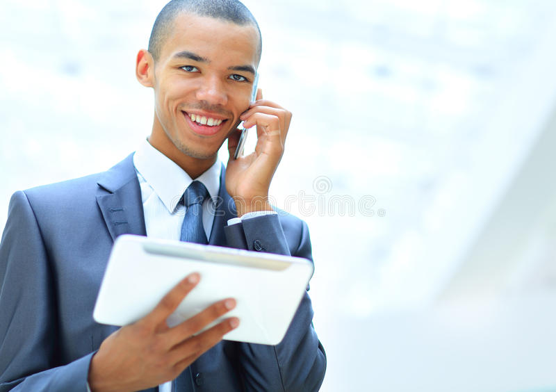 Imprenditore afroamericano che per mezzo del computer della compressa e parlando sul telefono immagini stock