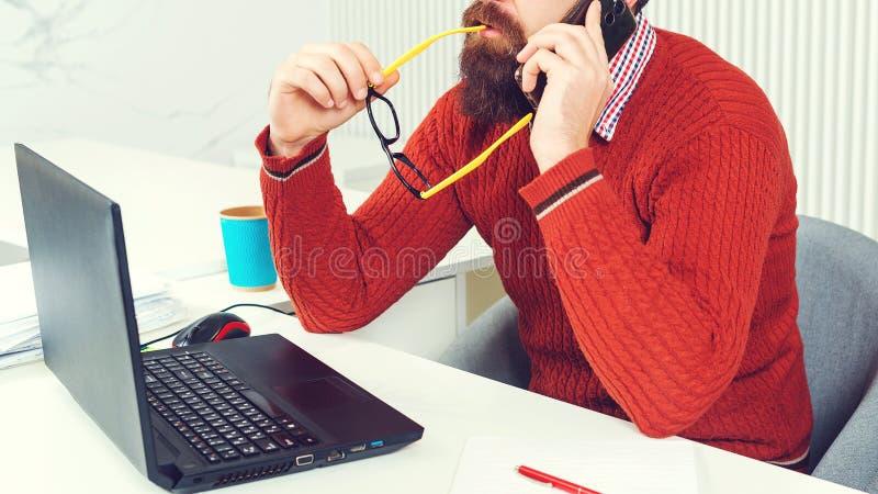 Imprenditore barbuto che lavora in ufficio Uomo che usa il portatile contemporaneo Imprenditore al suo posto di lavoro nel pensie fotografia stock libera da diritti