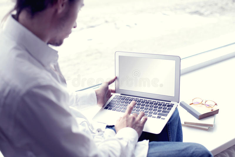 Imprenditore bello dell'uomo moderno dei pantaloni a vita bassa che lavora a casa facendo uso del computer portatile vicino alla  fotografie stock libere da diritti