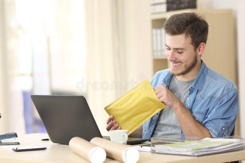 Imprenditore che apre una busta riempita fotografie stock libere da diritti