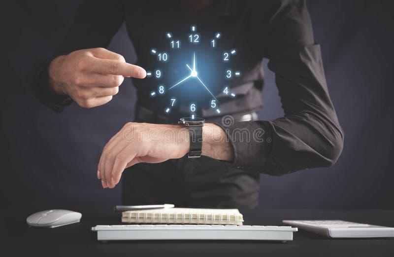 Imprenditore che mostra l'orologio in ufficio Gestione del tempo di attività immagini stock