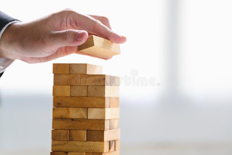 Imprenditore che organizza blocchi di legno e impilamento come torre a mano Progressi nell'organizzazione aziendale e nella cresc fotografia stock