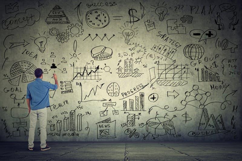 Imprenditore dell'uomo di affari che scrive alcuni nuovi calcoli di progetto sulla parete grigia immagini stock