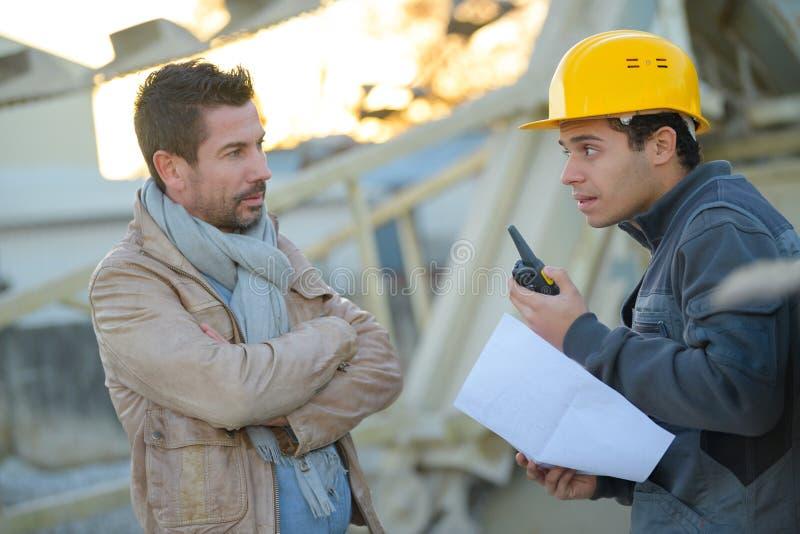 Imprenditore e costruttore sul cantiere facendo uso del walkie-talkie fotografie stock libere da diritti