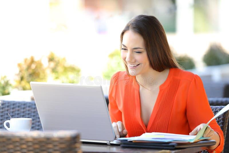 Imprenditore felice che lavora online in una caffetteria fotografia stock