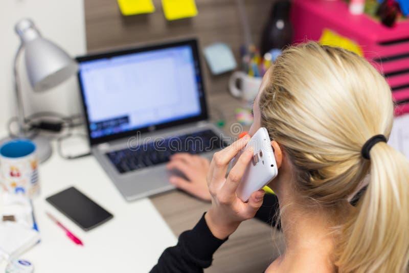Imprenditore femminile che parla sul telefono cellulare nel luogo di lavoro creativo moderno variopinto immagini stock