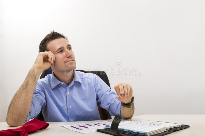 Imprenditore giovane di pensiero all'ufficio immagini stock