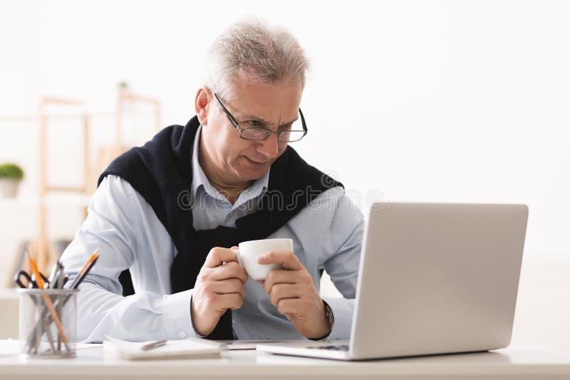 Imprenditore senior che mangia resto, caffè bevente e lavorante al computer portatile fotografia stock libera da diritti