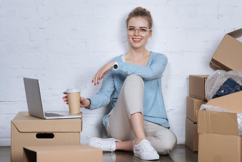imprenditore sorridente con caffè da andare sedersi sul pavimento immagini stock libere da diritti