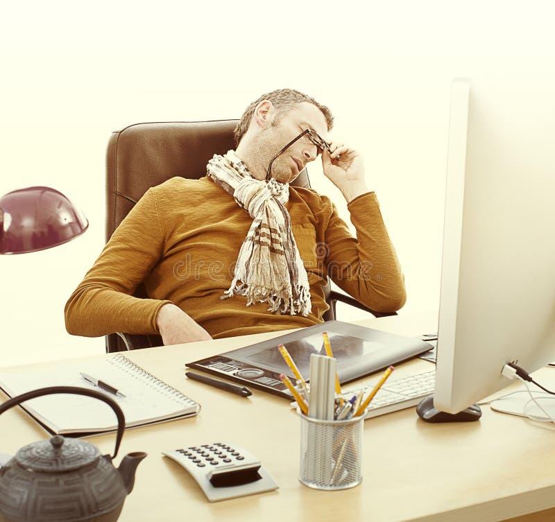 Imprenditore stanco che dorme al suo scrittorio, sovraccaricato dal lavoro tardi immagini stock libere da diritti