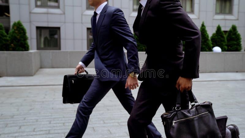 Imprenditori che corrono alla riunione importante con i partner, lavoro stressante, traffico fotografie stock