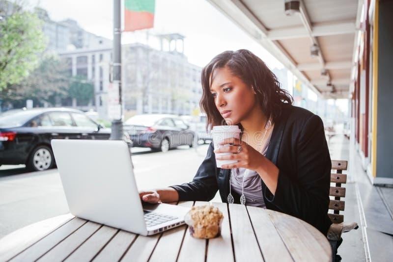 imprenditrice afroamericana che lavora sul suo computer portatile in un bar all'aperto fotografia stock