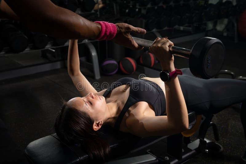 Imprensa de banco de ajuda da mulher do instrutor pessoal no gym, treinando com barbell imagem de stock