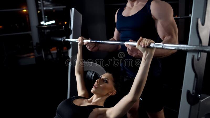 Imprensa de banco fazendo fêmea do barbell no gym, exercício sob a supervisão do instrutor fotos de stock