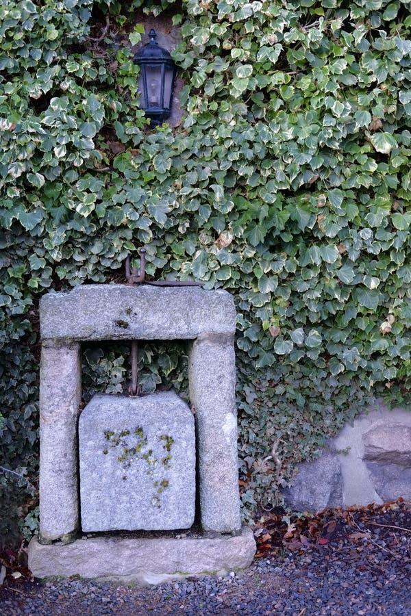 Imprensa de queijo antiga feita na pedra do granito imagem de stock