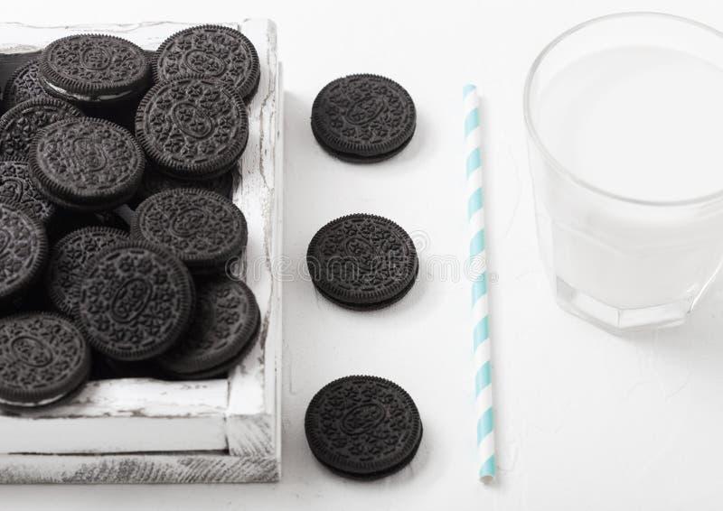 Imprense a cookie preta que consiste em duas bolachas do chocolate com o creme que enche-se com o vidro do leite no fundo de pedr fotos de stock royalty free
