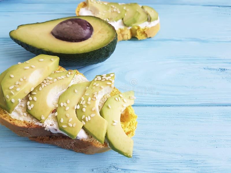 Imprense o abacate do freshwith e o brinde do vegetariano das sementes de sésamo em um de madeira imagens de stock royalty free