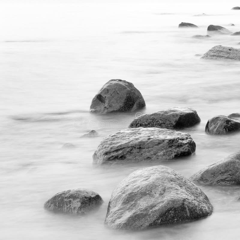 Impresión blanco y negro de la orilla de mar de la tarde con agua y de piedras en una playa imagenes de archivo