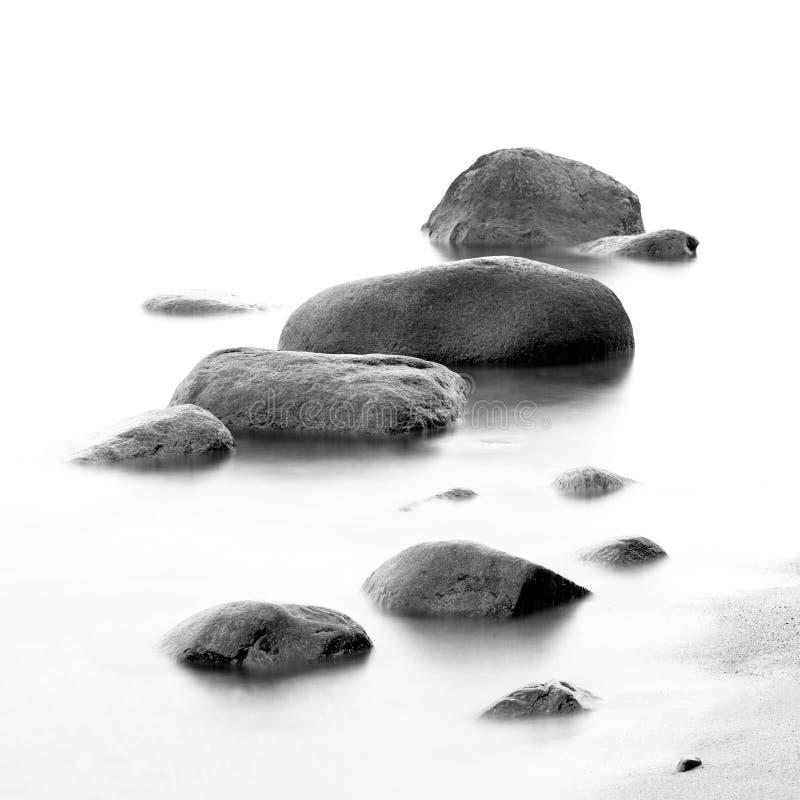 Impresión blanco y negro de la orilla de mar de la tarde con agua y de piedras en una playa imágenes de archivo libres de regalías