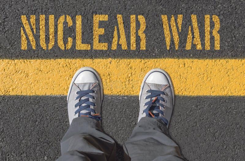 Impresión de la GUERRA NUCLEAR con las zapatillas de deporte en la carretera de asfalto fotografía de archivo libre de regalías