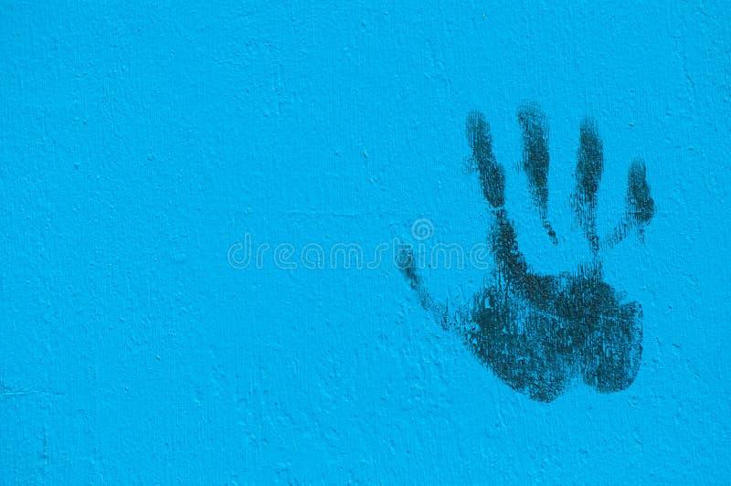 Impresión de la palma de la pintada en la pared pintada azul foto de archivo libre de regalías