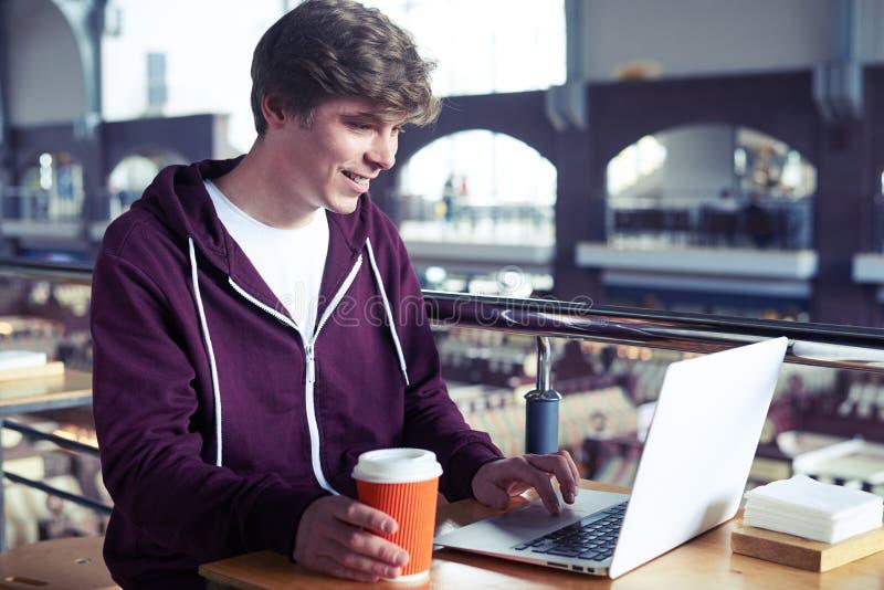 Impresión sonriente del individuo en ordenador portátil sobre la taza de café de papel fotografía de archivo