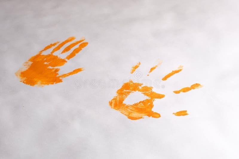 Impresiones anaranjadas de las manos en el Libro Blanco, palmas del ` s de los niños del ` s de los niños con la pintura foto de archivo