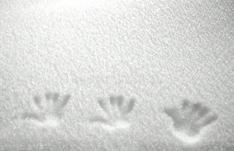 Impresiones de la mano en la nieve imagen de archivo libre de regalías