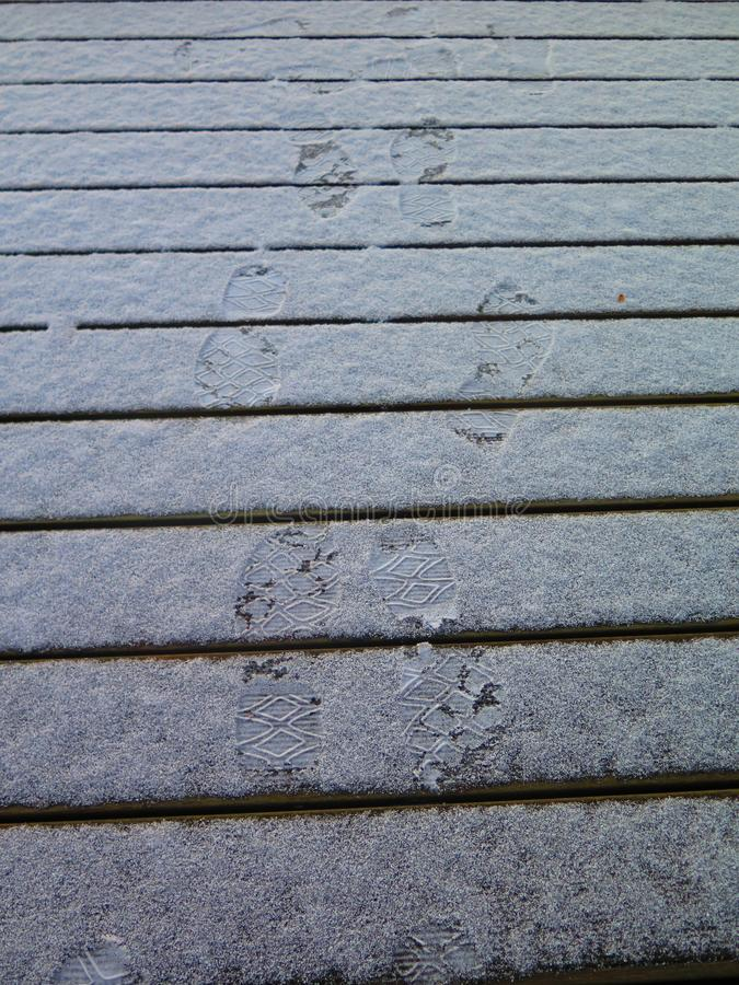 Impresiones del pie en decking nevado fotos de archivo
