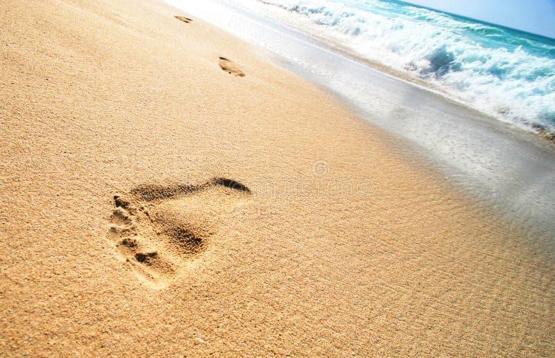 Impresiones del pie en la playa foto de archivo