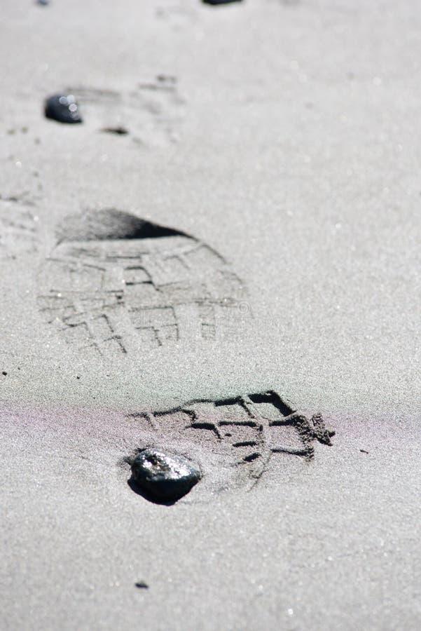 Impresiones del zapato en la arena fotos de archivo